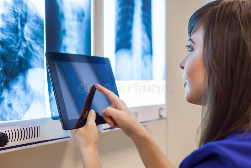 Kvinnlig doktor som använder en minnestavladator i ett sjukhus Hon är kläder royaltyfria foton