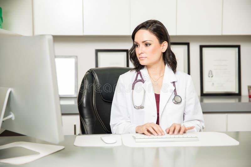 Kvinnlig doktor som arbetar i hennes kontor arkivbild