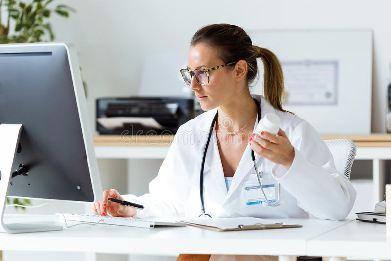 Kvinnlig doktor som arbetar med bärbara datorn i kontoret fotografering för bildbyråer