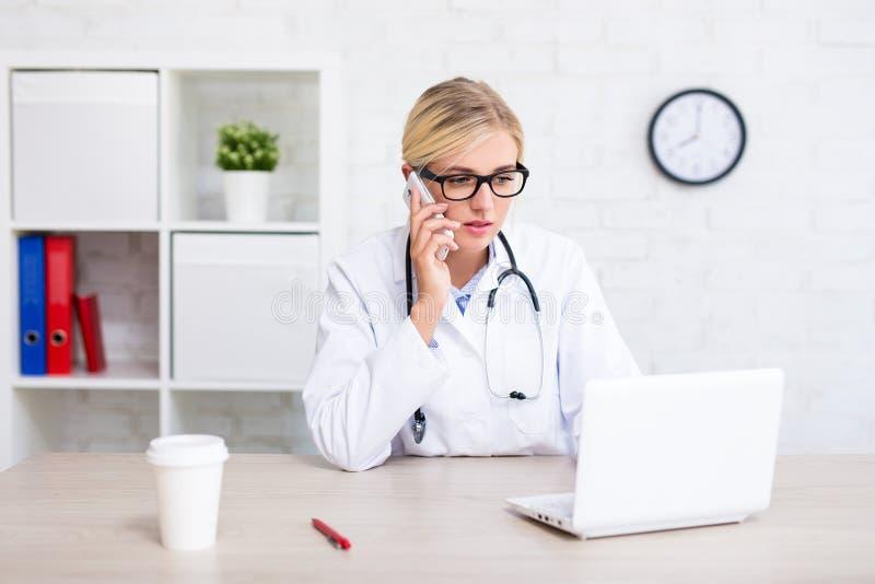 Kvinnlig doktor som arbetar med datoren och i regeringsställning talar vid telefonen royaltyfria foton