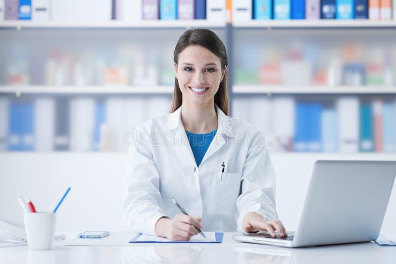Kvinnlig doktor som arbetar på kontorsskrivbordet royaltyfri fotografi
