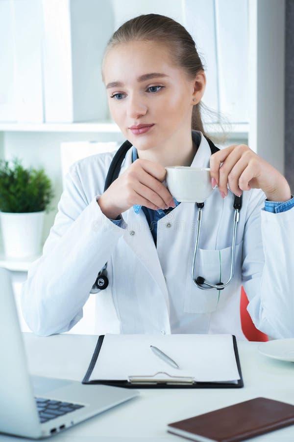 Kvinnlig doktor som arbetar på medicinskt sakkunskap- och drinkkaffe, medan sitta på skrivbordet framme av bärbara datorn Ung ter arkivfoton