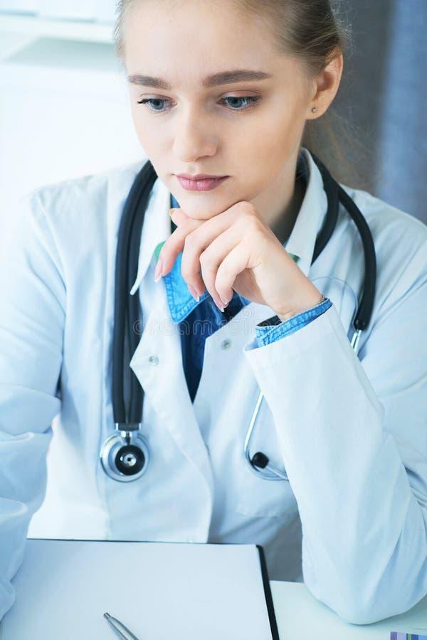 Kvinnlig doktor som arbetar p? medicinsk sakkunskap, medan sitta p? skrivbordet framme av b?rbara datorn Den unga terapeuten ser  royaltyfri fotografi
