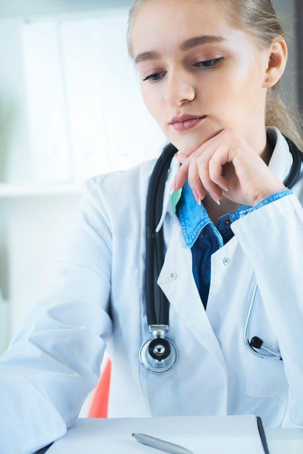 Kvinnlig doktor som arbetar p? medicinsk sakkunskap, medan sitta p? skrivbordet framme av b?rbara datorn Den unga terapeuten ser  arkivbilder