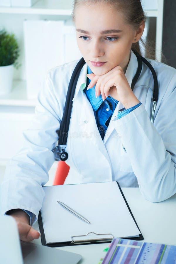 Kvinnlig doktor som arbetar p? medicinsk sakkunskap, medan sitta p? skrivbordet framme av b?rbara datorn Den unga terapeuten ser  arkivfoton