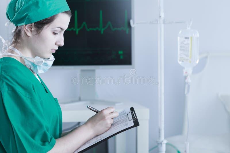Kvinnlig doktor som avslutar medicinsk dokumentation arkivfoton