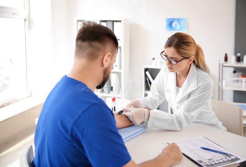 Kvinnlig doktor som drar en blodprövkopia av den manliga patienten i klinik arkivfoto