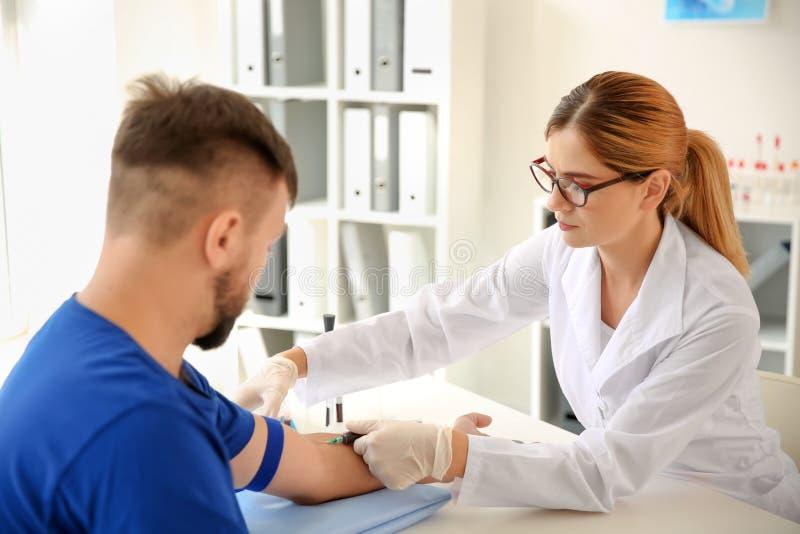 Kvinnlig doktor som drar en blodprövkopia av den manliga patienten i klinik arkivfoton