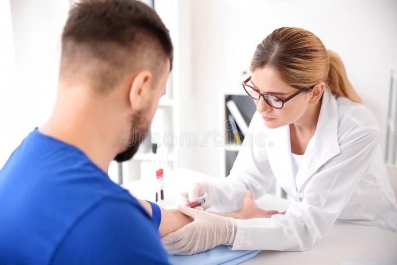 Kvinnlig doktor som drar en blodprövkopia av den manliga patienten i klinik royaltyfria bilder