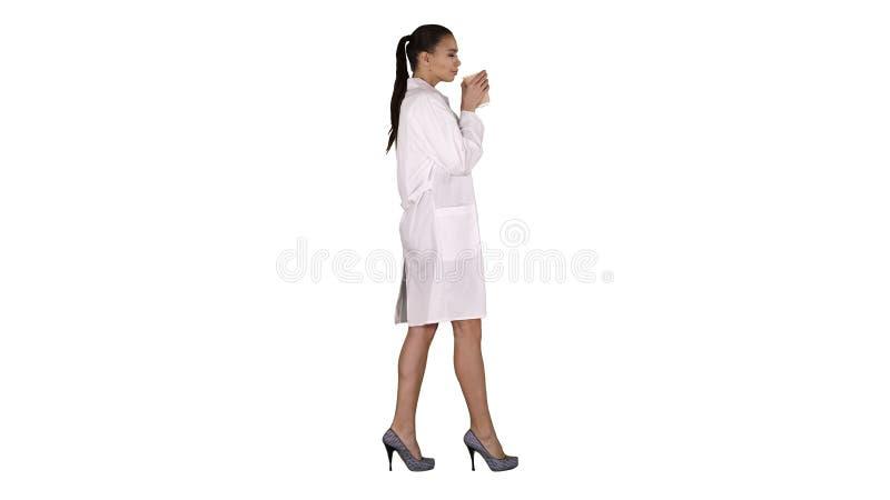 Kvinnlig doktor som dricker kaffe och går på vit bakgrund arkivbild