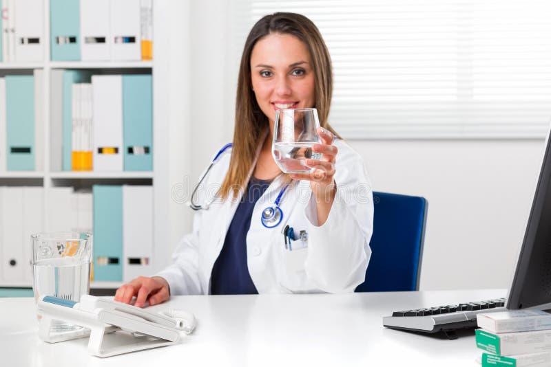 Kvinnlig doktor som erbjuder ett exponeringsglas av vatten royaltyfria foton