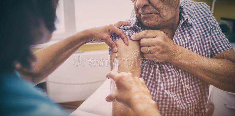 Kvinnlig doktor som ger en injektion till en patient fotografering för bildbyråer