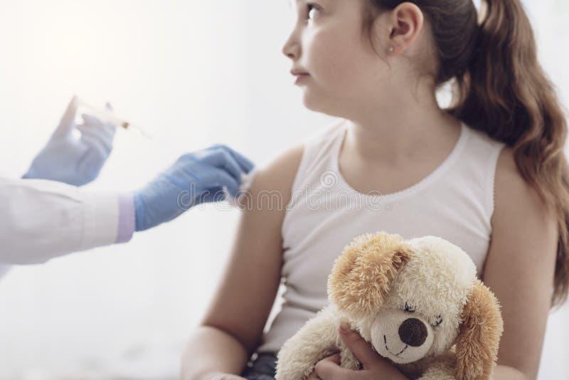 Kvinnlig doktor som ger en injektion till en ung gullig flicka royaltyfria bilder