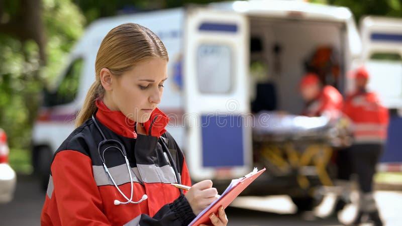 Kvinnlig doktor som håller sjukdomshistorier, ambulansbesättning som transporterar patienten arkivbild