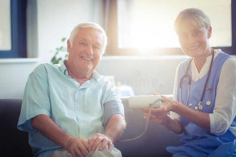 Kvinnlig doktor som kontrollerar blodtryck av den höga mannen royaltyfri foto