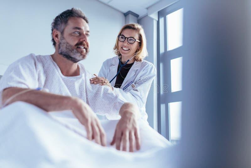 Kvinnlig doktor som kontrollerar den manliga patienten i sjukhusrum royaltyfri bild