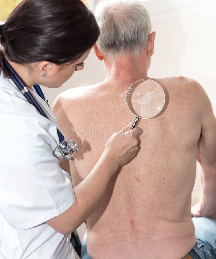 Kvinnlig doktor som kontrollerar hud av den höga patienten royaltyfria bilder