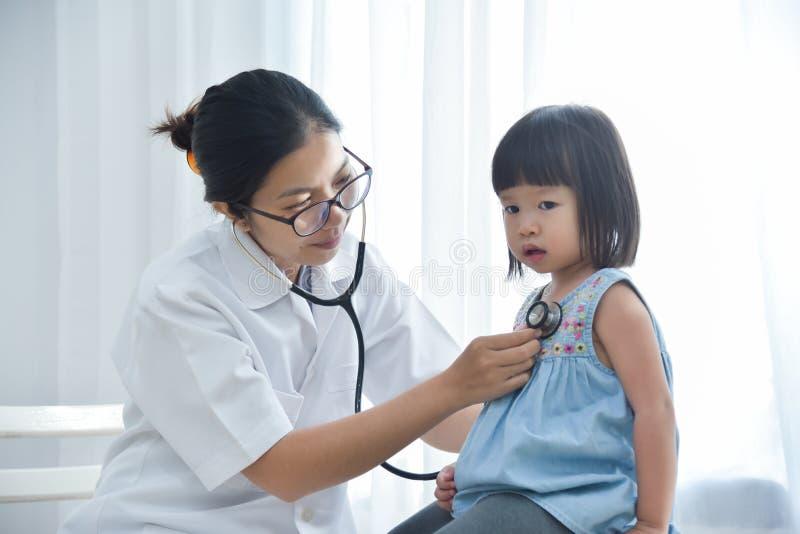 Kvinnlig doktor som lite undersöker flickan royaltyfri bild