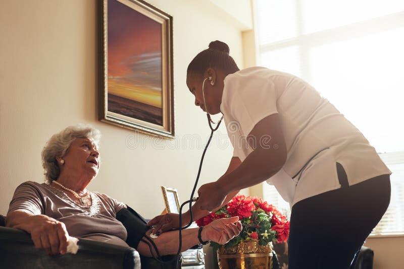 Kvinnlig doktor som mäter blodtryck av den gamla damen royaltyfria foton