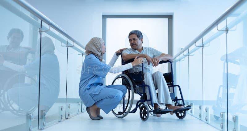 Kvinnlig doktor som påverkar varandra med den rörelsehindrade manliga patienten i korridoren royaltyfri bild