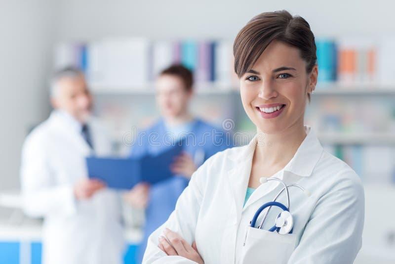 Kvinnlig doktor som poserar i kontoret arkivbild