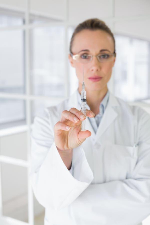 Kvinnlig doktor som rymmer en injektion i sjukhus royaltyfri fotografi