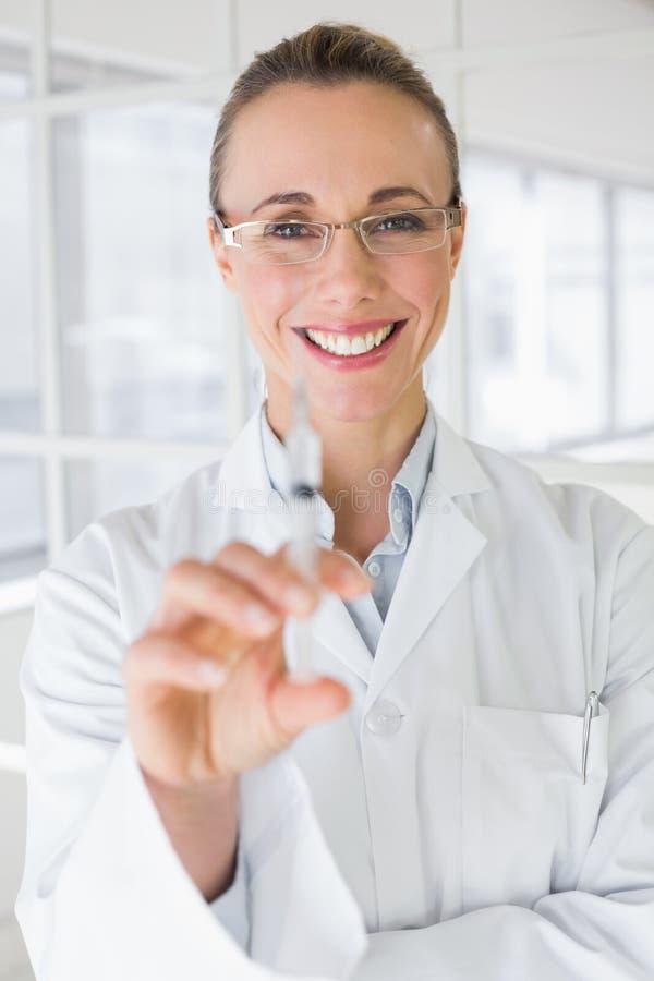 Kvinnlig doktor som rymmer en injektion i sjukhus arkivfoton