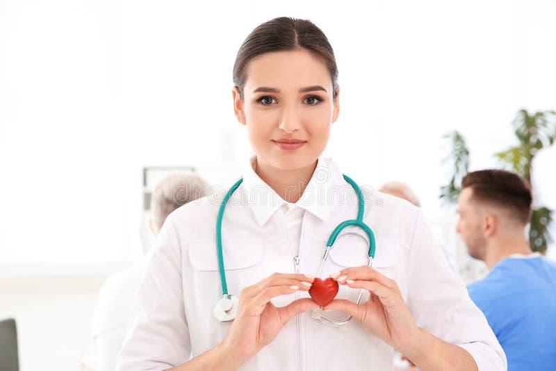 Kvinnlig doktor som rymmer liten hjärta i klinik arkivfoto