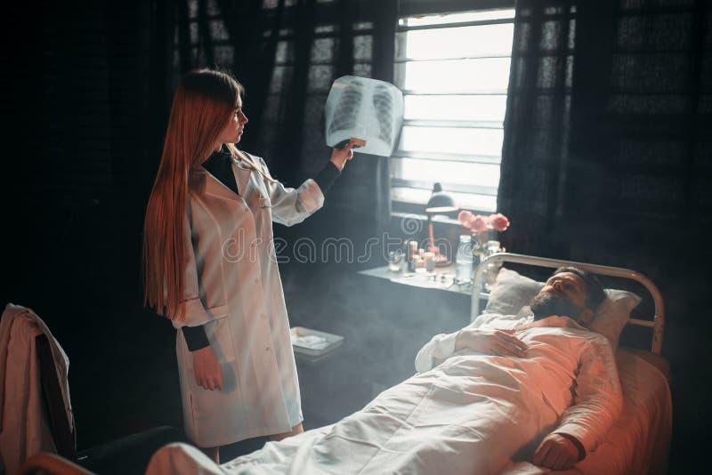 Kvinnlig doktor som ser röntgenstrålebilden av den sjuka mannen royaltyfria foton