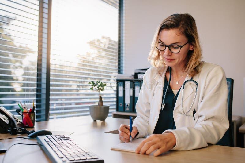 Kvinnlig doktor som sitter på skrivbordet och skriva royaltyfri bild