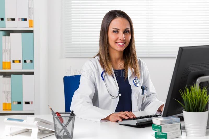 Kvinnlig doktor som sitts på skrivbordet genom att använda datoren arkivfoton