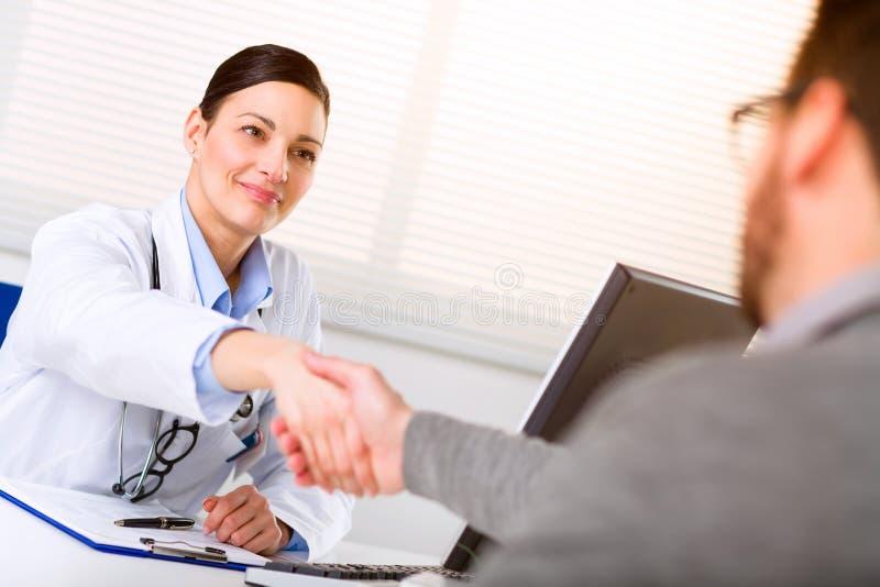 Kvinnlig doktor som skakar handen till den manliga patienten royaltyfri bild