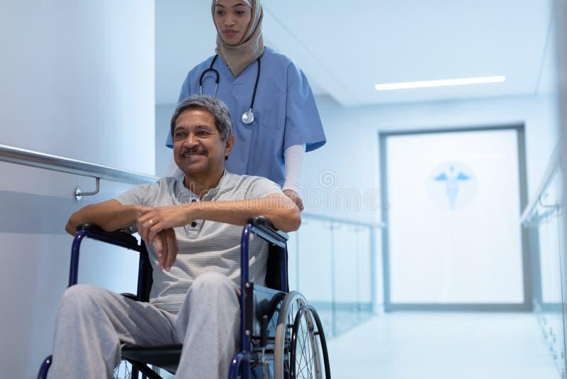 Kvinnlig doktor som skjuter den manliga patienten i rullstol på korridoren arkivfoton