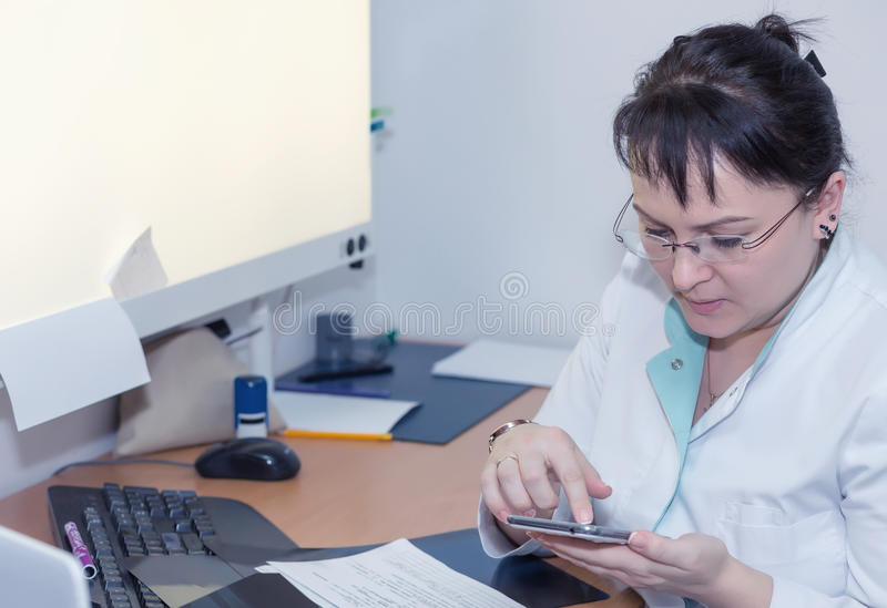 Kvinnlig doktor som surfar internet med hennes smartphome royaltyfri fotografi