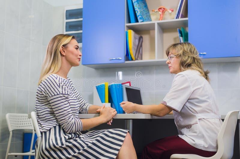 Kvinnlig doktor som talar med patienten i doktorskontor arkivbild