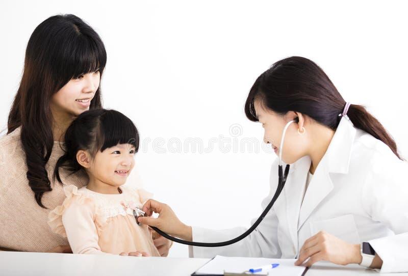 Kvinnlig doktor som undersöker en barnpatient arkivfoto