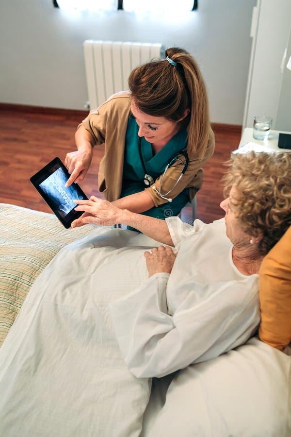 Kvinnlig doktor som visar en röntgenstråle på minnestavlan arkivbild