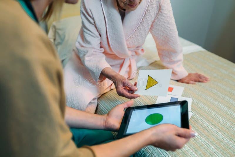 Kvinnlig doktor som visar geometriska former till den äldre patienten fotografering för bildbyråer