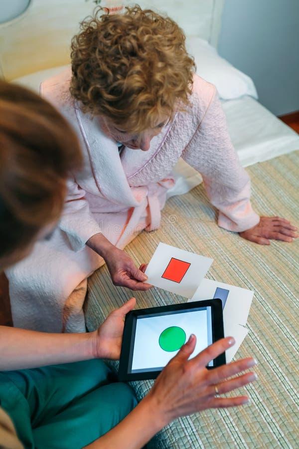 Kvinnlig doktor som visar geometriska former till den äldre patienten arkivfoton