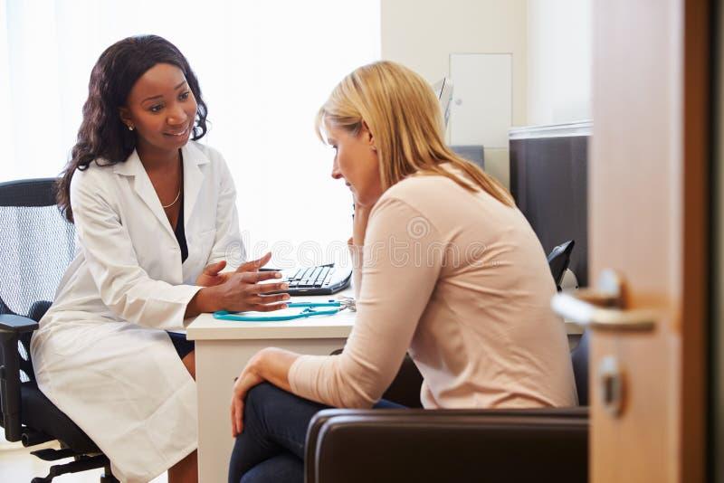 Kvinnlig doktor Treating Patient Suffering med fördjupning royaltyfri bild