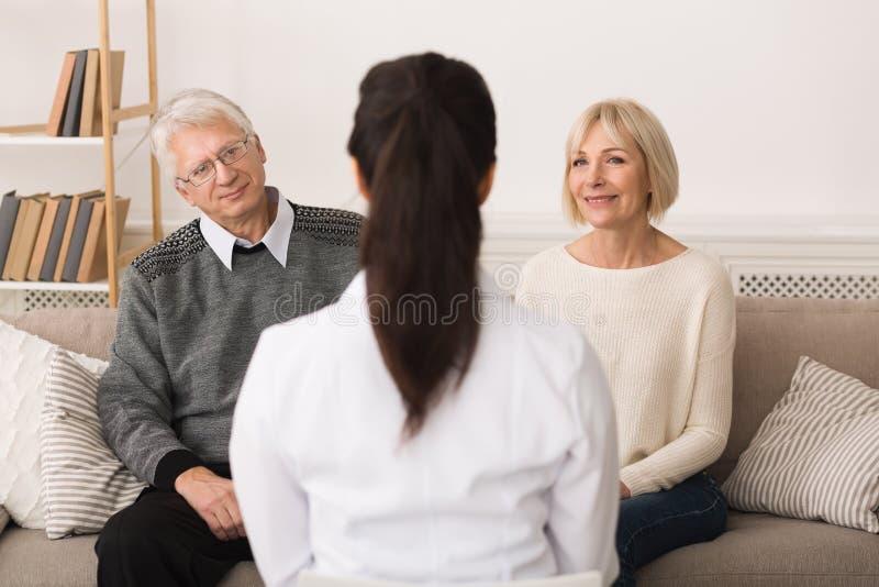 Kvinnlig doktor Visiting Senior Couple som talar till dem royaltyfri fotografi