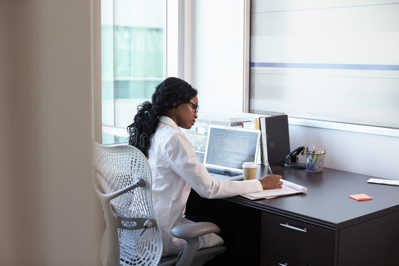 Kvinnlig doktor Wearing White Coat i regeringsställning som arbetar på skrivbordet royaltyfria bilder