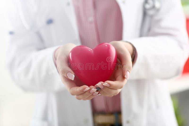 Kvinnlig doktorsh?ll i armar och r?d leksak f?r r?kning royaltyfri bild