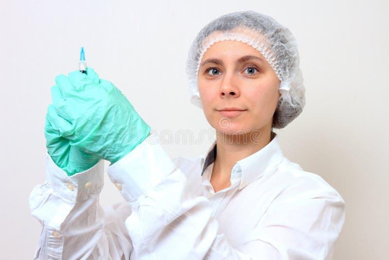 Kvinnlig doktorsinnehavinjektionsspruta med injektionen royaltyfri fotografi