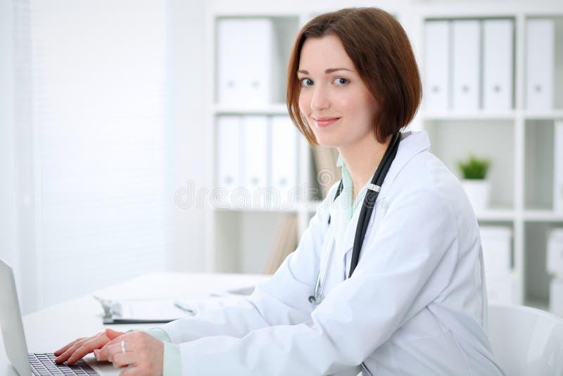 Kvinnlig doktorsmaskinskrivning för ung brunett på bärbar datorcomoputer, medan sitta på tabellen i sjukhuskontor Hälsa ca arkivbild