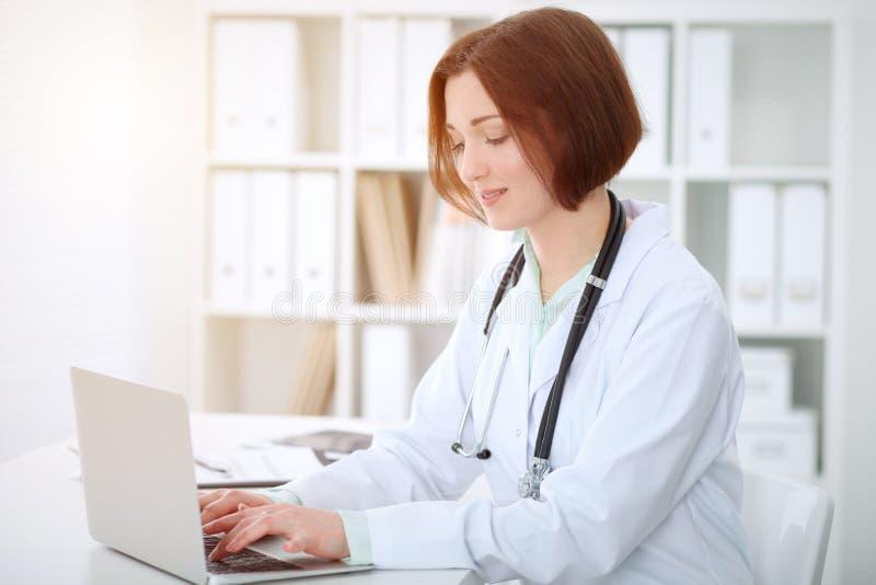 Kvinnlig doktorsmaskinskrivning för ung brunett på bärbar datorcomoputer, medan sitta på tabellen i sjukhuskontor Hälsa ca royaltyfria bilder