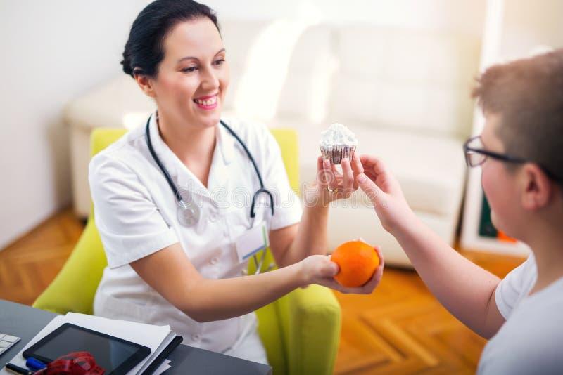 Kvinnlig doktorsnäringsfysiolog och tonåringpatient arkivbild