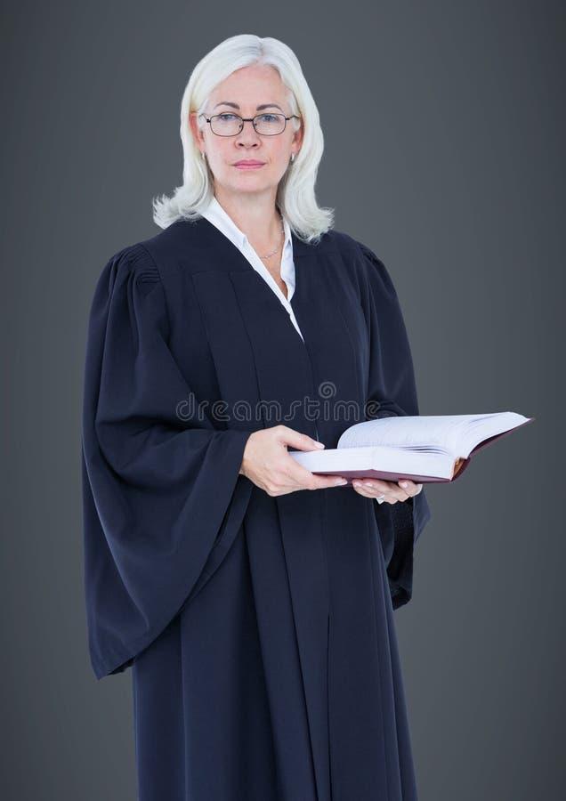 Kvinnlig domare med auktionsklubban mot grå bakgrund royaltyfria bilder