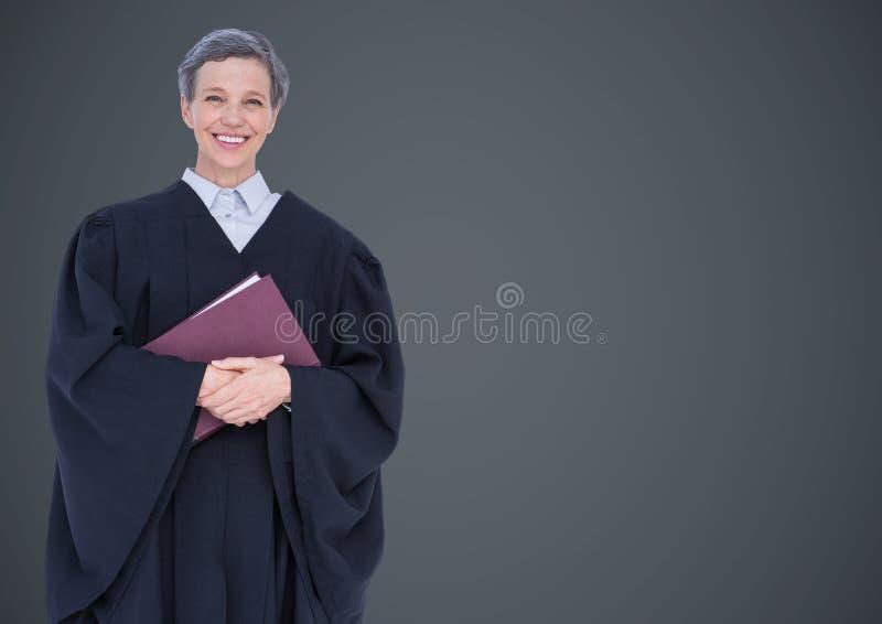 Kvinnlig domare med boken mot den gråa väggen arkivfoto