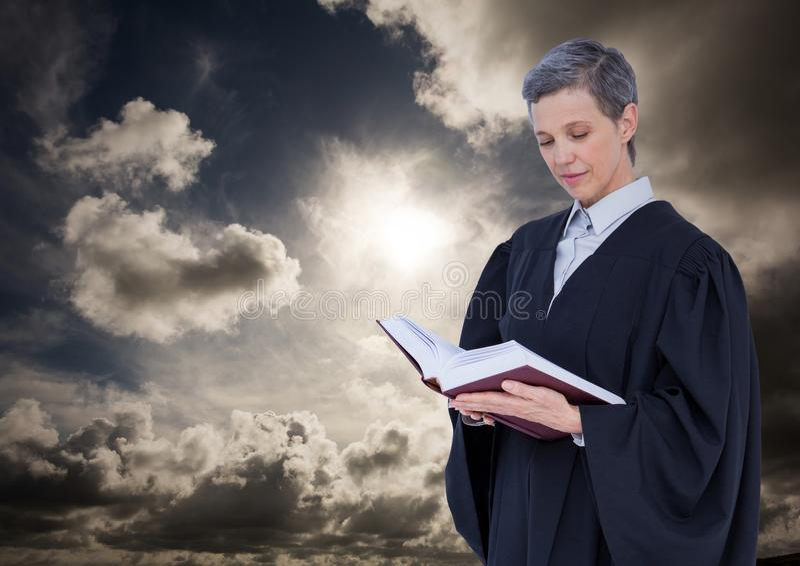 Kvinnlig domareläsning mot molnig himmel royaltyfri fotografi